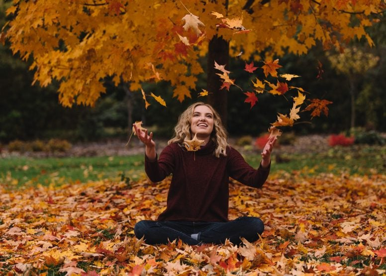 Happy young woman sitting in leaves