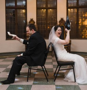 Couple playing shoe game at their wedding reception