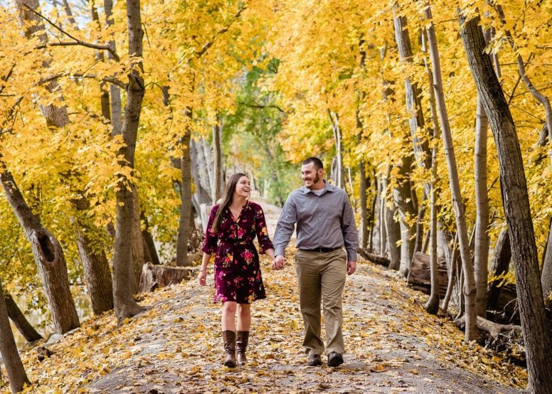 Engaged couple walking and laughing through leaves