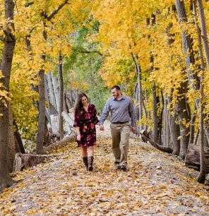 Fall engagement session with couple walking in leave covered path